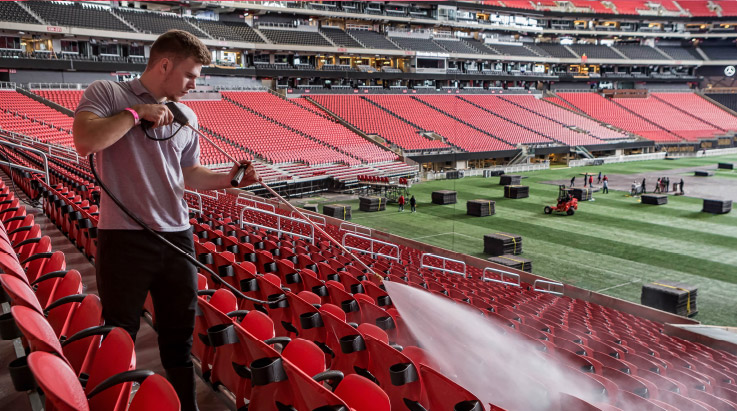 Level Seven staff member pressure washing a stadium